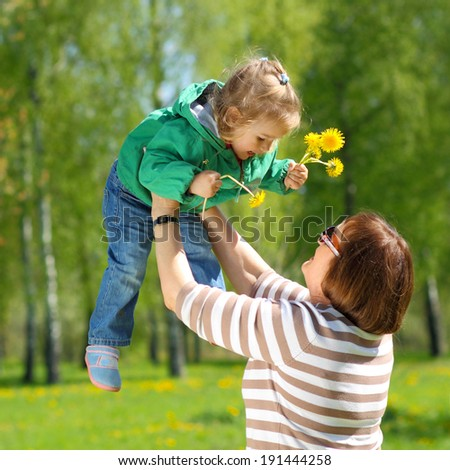 Grandmother and little granddaughter playing on the meadow of yellow dandelions. Grandmother throws up his granddaughter - stock photo