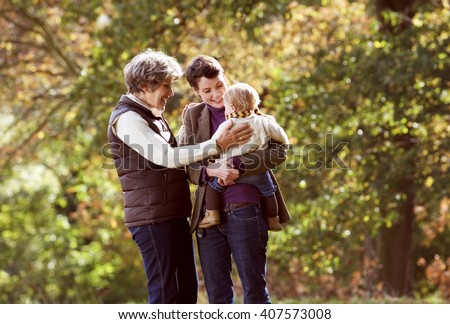 Grandmother and mother smiling at baby - stock photo