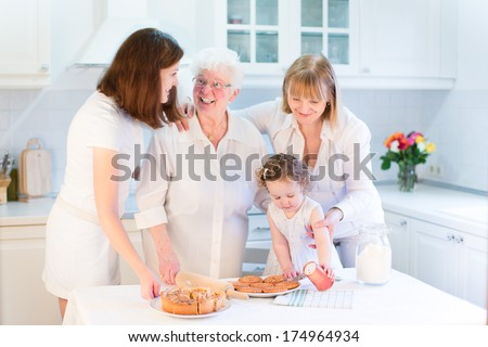 Grandmother baking an apple pie with her daughter, granddaughter and great grand daughter, a cute toddler girl, in a sunny white kitchen - stock photo