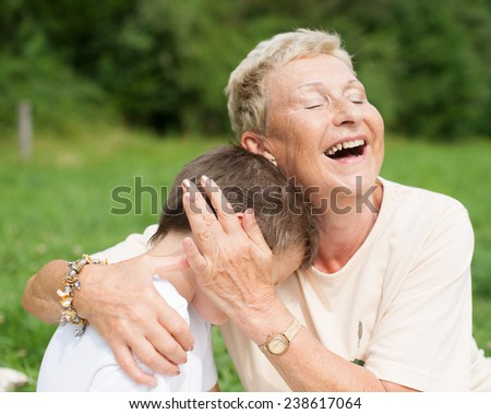 Grandmother caressing and hugging grandson - stock photo