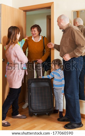 Grandmother coming to family with two children home - stock photo