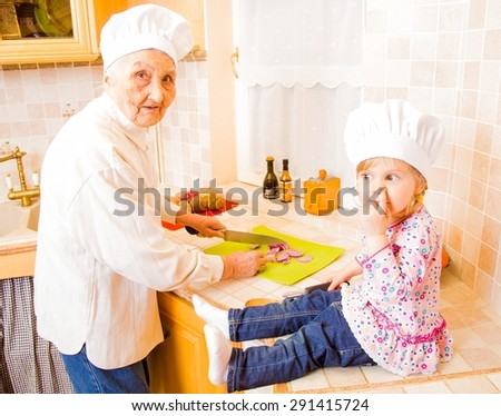Grandmother cooking together with grand-daughter in the kitchen. - stock photo