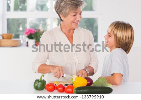 Grandmother cutting vegetables looking at her grandson in kitchen - stock photo