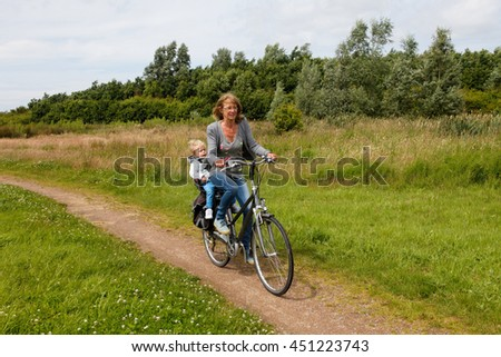 grandmother cycling with grandchild in nature on bike path
