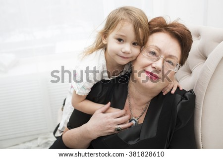 Grandmother embrace the granddaughter in the room - stock photo