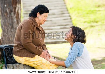 Grandmother facing granddaughter touching heads outdoors, lovely picture displaying love between people. - stock photo