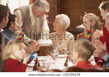 Grandmother getting her birthday cake at the table with family - stock photo