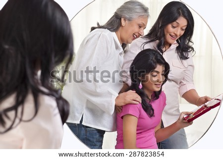 Grandmother gifting jewelry to her granddaughter - stock photo