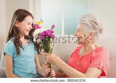 Grandmother giving a bunch of flowers to her granddaughter - stock photo