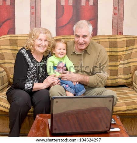 Grandmother, grandfather and granddaughter using technology. Happy senior couple and loving baby