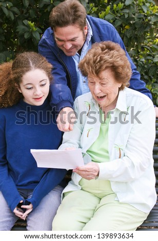 Grandmother, her grown son, and teenage granddaughter reading a letter together .