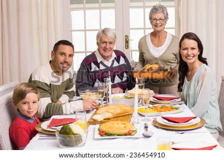 Grandmother holding turkey roast with family at christmas at home in the living room - stock photo