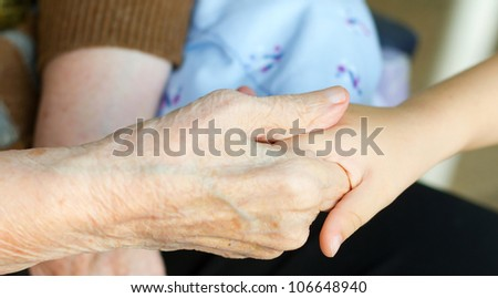 Grandmother holds the hand of his grandson - stock photo