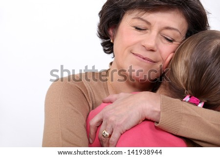 Grandmother hugging her granddaughter - stock photo