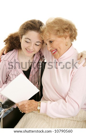 Grandmother in wheelchair reading a mother's day (or get well) card from her granddaughter.  White background. - stock photo