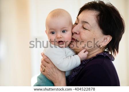 Grandmother is kissing her baby grandson - indoors scene - stock photo