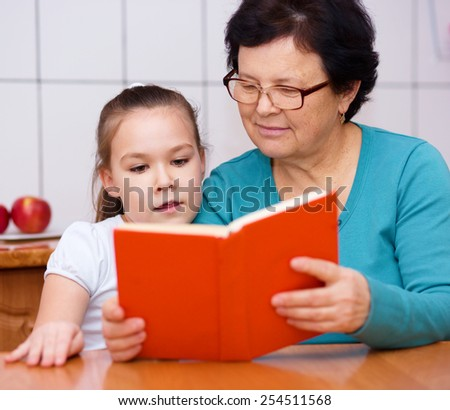 Grandmother is reading book with her granddaughter, indoors - stock photo