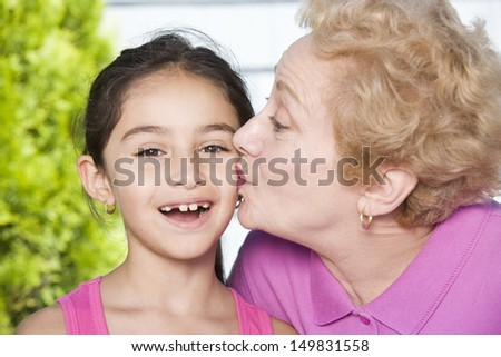 Grandmother kissing granddaughter on cheek