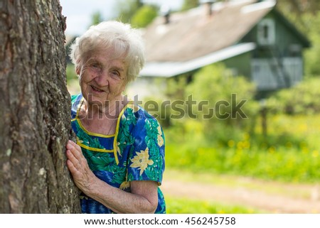 Grandmother looks out from behind a tree near his home. - stock photo