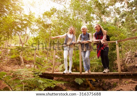 Grandmother, mother and daughter on a bridge in a forest - stock photo