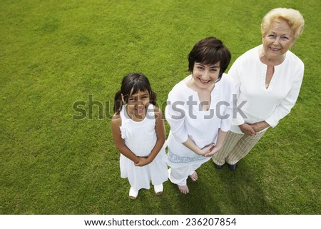 Grandmother, Mother and Daughter Standing in a Row - stock photo