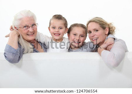 Grandmother, mother and daughters behind white sign - stock photo