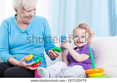 Grandmother playing cheerfully with grandson in the living room  - stock photo