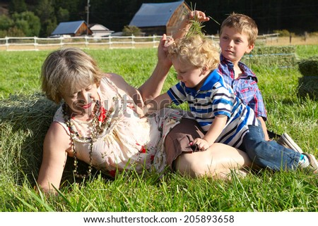 Grandmother playing in the hayfield with her grandsons - stock photo
