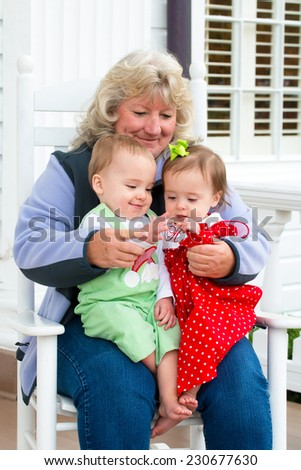 Grandmother playing with twin babies while sitting on rocking chair at home on porch - stock photo