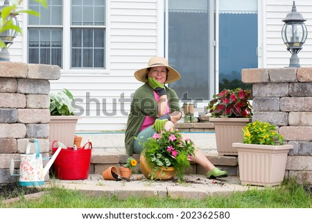 Grandmother potting up plants on her patio sitting on the brick step surrounded by fresh seedlings and flowerpots looking pensively at the camera with her chin on her hand with a friendly smile - stock photo