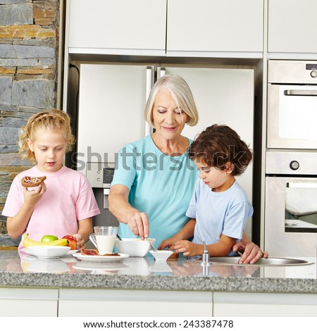 Grandmother preparing a healthy breakfast for her two grandchildren in the kitchen - stock photo