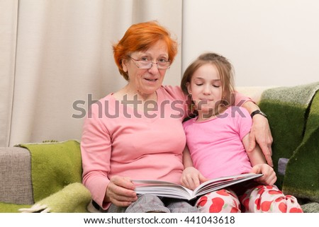 grandmother read book  for granddaughter, they sit together and smile - stock photo