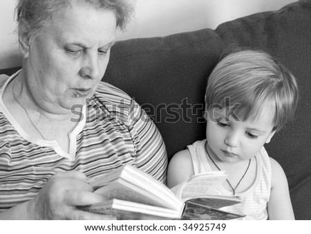 grandmother read the book for her grandson. black and white - stock photo