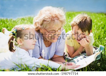 grandmother reading book to grandchildren outdoors - stock photo