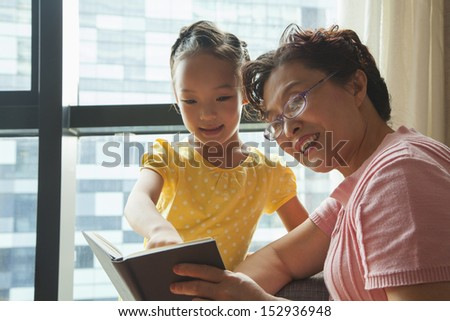 Grandmother reading book to her granddaughter - stock photo