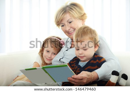Grandmother reading from a book for grandchildren at home - stock photo