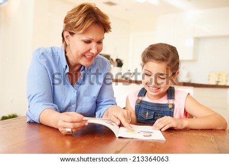 Grandmother Reading With Granddaughter At Home