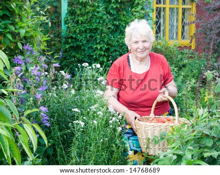 Grandmother showing basket with strawberries in the garden