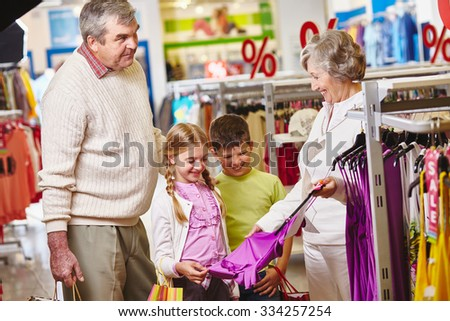 Grandmother showing new tanktop for granddaughter in the mall - stock photo