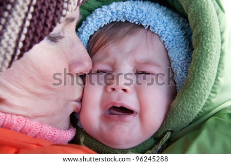 Grandmother soothing and kissing crying baby. - stock photo