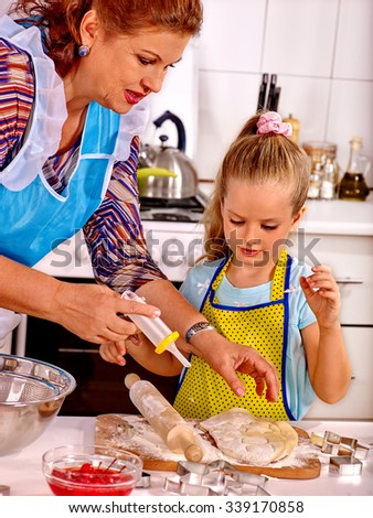 Grandmother teach her granddaughter baking cookies. - stock photo