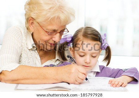 Grandmother teaches to write letters her granddaughter - stock photo