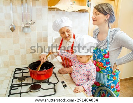 Grandmother teaching grand-daughter how to cook. - stock photo