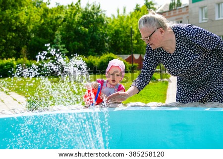 Grandmother teaching her granddaughter how to pour water from a fountain in a bucket - stock photo