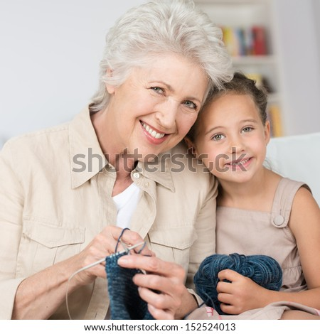Grandmother teaching her pretty smiling little granddaughter to knit as they sit close together on a sofa in the living room