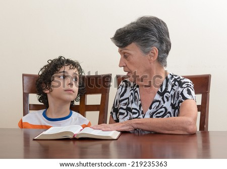 Grandmother teaching the Holy Bible to her grandson. Hispanic family studying the word of God in their daily Christian devotional. Reverence to God learning from His word.