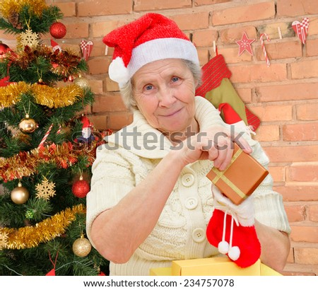 grandmother wearing Santa Claus hat with christmas gifts