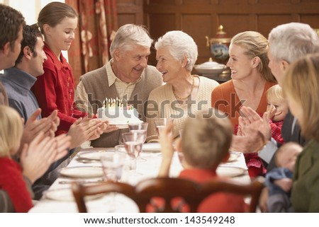 Grandmother with birthday cake and family at dinner table - stock photo