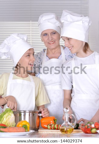 Grandmother with grandchildren preparing dinner for the whole family - stock photo