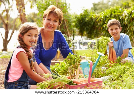 Grandmother With Grandchildren Working On Allotment - stock photo